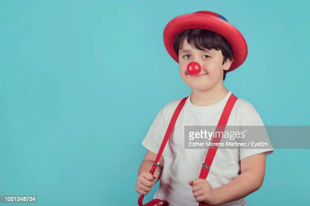 portrait of boy wearing joker costume while standing against blue background - clown's nose stock photos and pictures