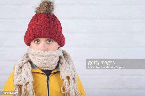 portrait of boy wearing knit hat and warm clothing against wall - wool stock pictures, royalty-free photos & images