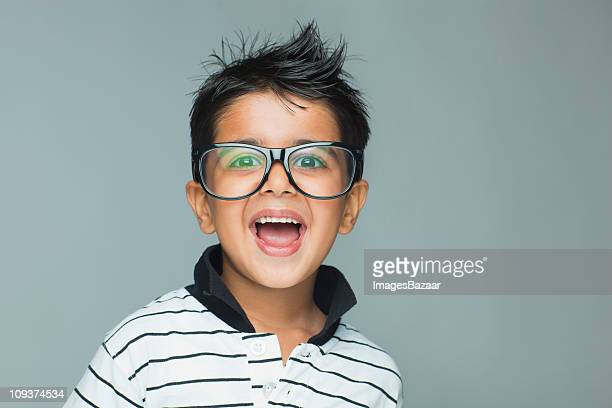 Portrait of boy (6-7) wearing large glasses laughing