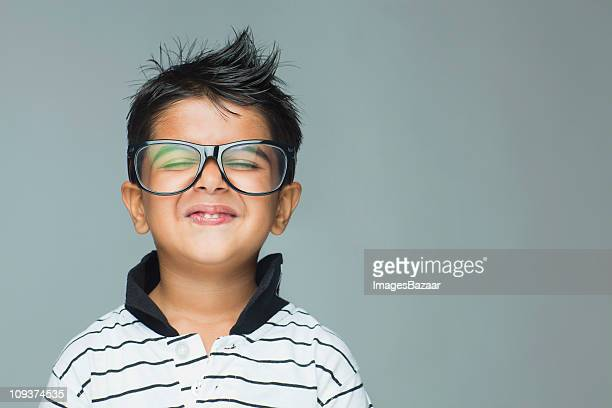 Portrait of boy (6-7) wearing large glasses making funny face