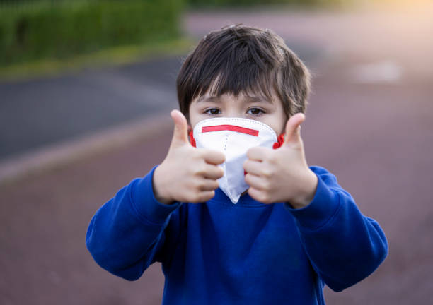 portrait of boy wearing mask gesturing outdoors - children mask stock pictures, royalty-free photos & images