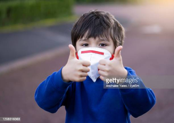 portrait of boy wearing mask gesturing outdoors - child stock pictures, royalty-free photos & images