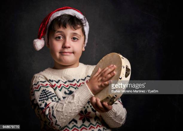 Portrait Of Boy Wearing Santa Hat Playing Tambourine While Standing Against Black Background