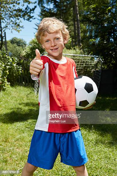 Portrait of boy wearing soccer uniform holding soccer ball and giving thumbs up in garden