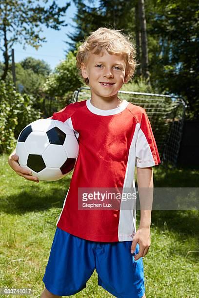 portrait of boy wearing soccer uniform holding soccer ball in garden - nur jungen stock-fotos und bilder
