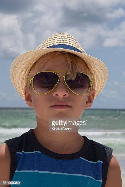 portrait of boy wearing straw hat and sunglasses on beach, anna maria island, florida, usa - anna maria island stock pictures, royalty-free photos & images