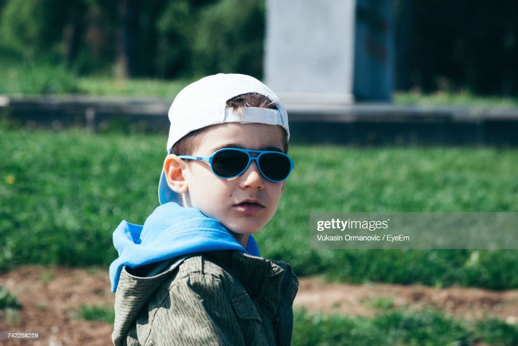 8b05fa60793b Portrait Of Boy Wearing Sunglasses And Cap Looking Over Shoulder Outdoors :  Stock-Foto