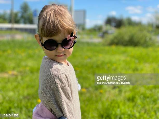 portrait of boy wearing sunglasses on field - unknown gender stock pictures, royalty-free photos & images