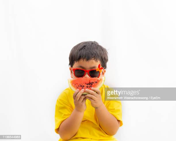 portrait of boy wearing sunglasses while having watermelon against white background - one boy only stock pictures, royalty-free photos & images