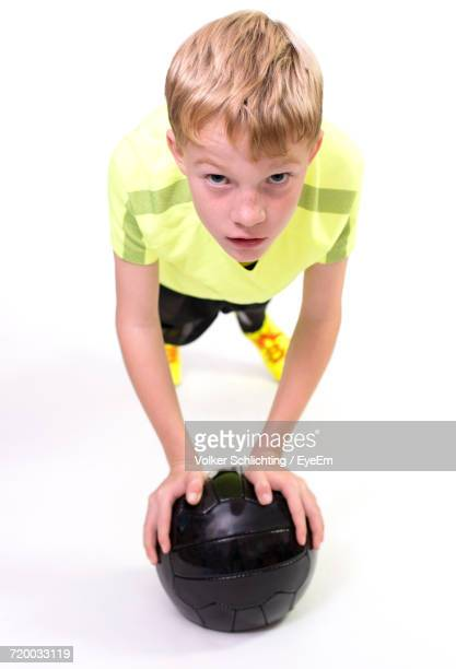 Portrait Of Boy With Black Soccer Ball On White Background