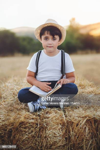 Portrait Of Boy With Book Sitting On Hay Bales