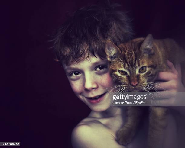 Portrait Of Boy With Cat Against Black Background