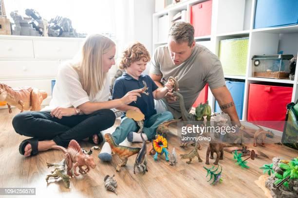 retrato de menino com deficiência brincar com brinquedos em casa com os pais - grupo grande de objetos - fotografias e filmes do acervo