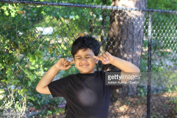 portrait of boy with fingers in ears against chainlink fence - fingers in ears stock pictures, royalty-free photos & images
