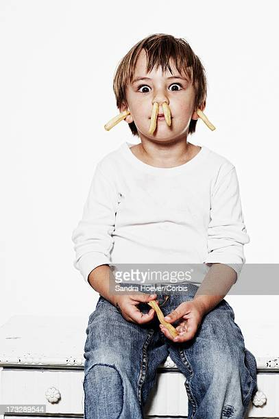 portrait of boy (6-7) with french fries in nose and ears - fries stock-fotos und bilder