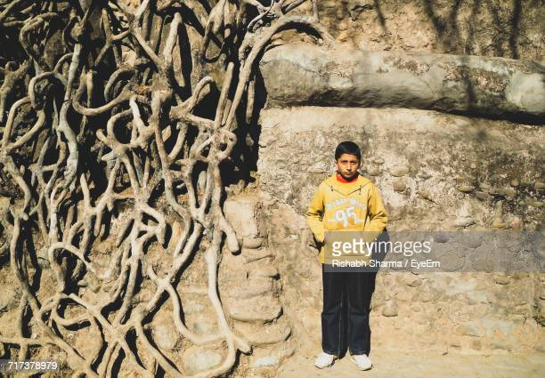 Portrait Of Boy With Hands In Pockets Standing By Tree Roots Against Wall At Old Ruins