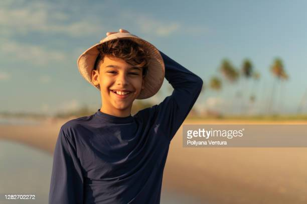 portrait of boy with hat on the beach - uv protection stock pictures, royalty-free photos & images