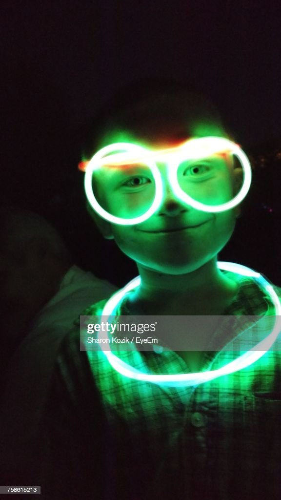 Portrait Of Boy With Illuminated Neon Ring And Eyeglasses In Darkroom : Stock Photo