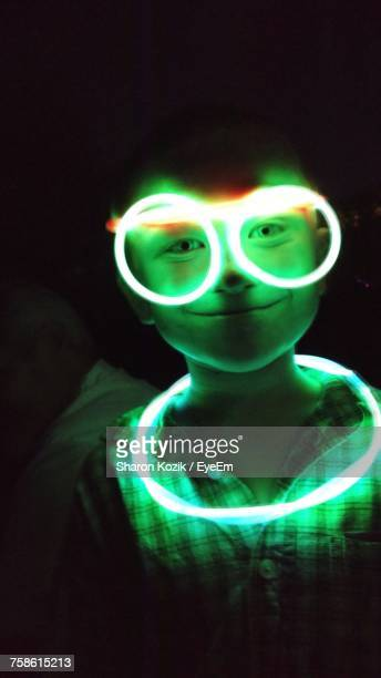 Portrait Of Boy With Illuminated Neon Ring And Eyeglasses In Darkroom