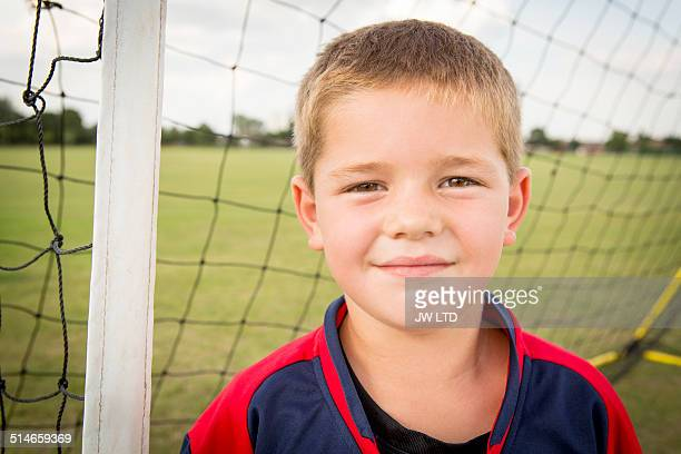 Portrait of boy with in football goal