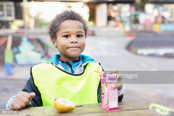 portrait of boy with juice box outside kindergarten - juice carton stock photos and pictures