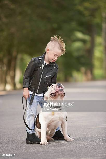 Portrait of boy with mohawk in leather jacket with bulldog