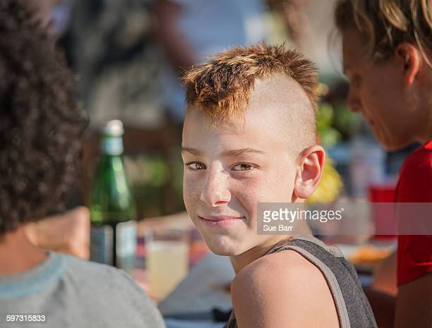 Portrait of boy with mohawk looking over shoulder at camera smiling