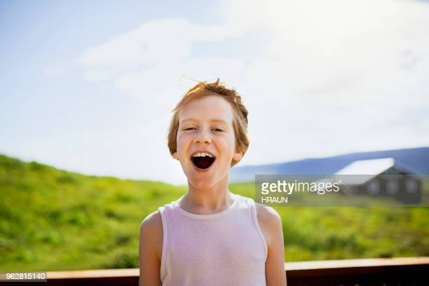 Portrait of boy with mouth open on patio