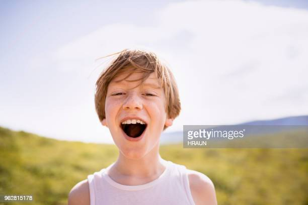 Portrait of boy with mouth open screaming on patio