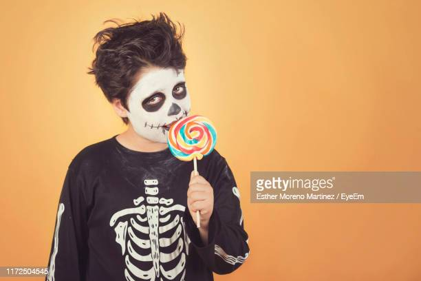 portrait of boy with painted face wearing costume while eating lollipop against orange background - human skeleton stock pictures, royalty-free photos & images