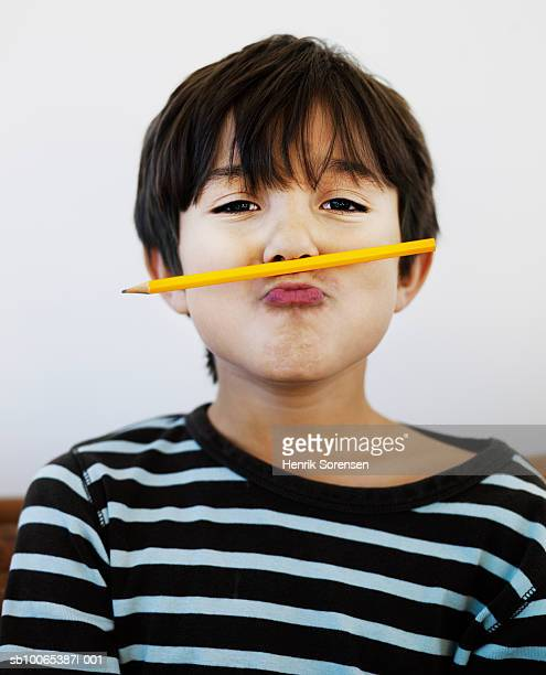 portrait of boy (8-9) with pencil under nose - nariz humano imagens e fotografias de stock