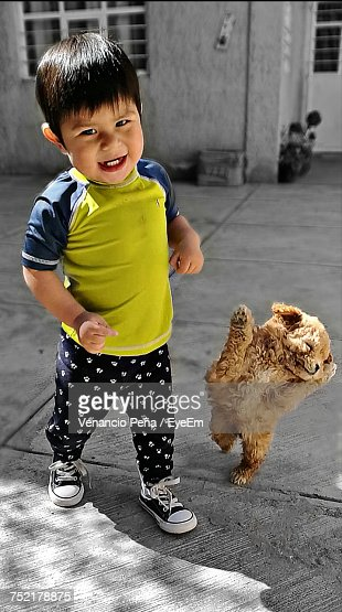 Portrait Of Boy With Puppy Dancing On Street