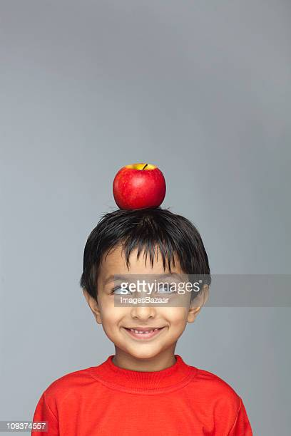 Portrait of boy (4-5) with red apple balanced on top of head