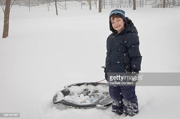 """portrait of boy with sled in snow - """"danielle donders"""" stock pictures, royalty-free photos & images"""