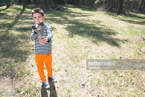 Portrait of boy with slingshot