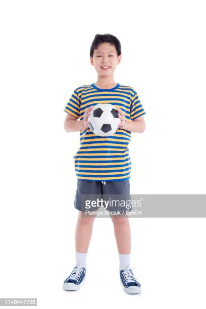 portrait of boy with soccer ball standing against white background - shorts stock pictures, royalty-free photos & images