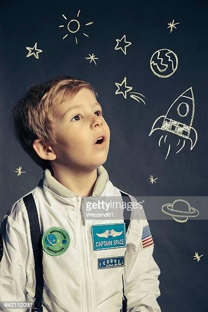 Portrait of boy with spacemansuit orbited by celestial bodies and luminaries
