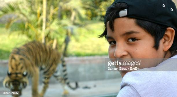 Portrait Of Boy With Tiger In Background At Zoo
