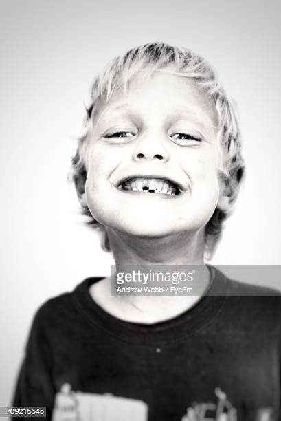 Portrait Of Boy With Toothy Smile Against White Background