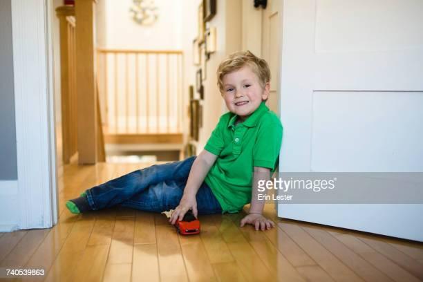 Portrait of boy with toy car sitting on floor