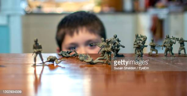 portrait of boy with toy soldiers  on  a table - army soldier toy stock pictures, royalty-free photos & images