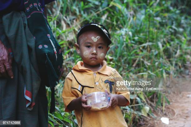 portrait of boy with traditional face painting sanding on field - ko ko htike aung stock pictures, royalty-free photos & images