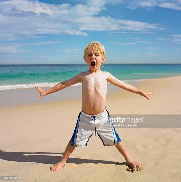 portrait of boy yelling at beach - knaben in badehosen stock-fotos und bilder