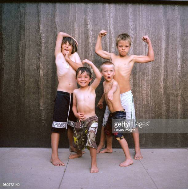 Portrait of boys flexing muscles while standing against wall