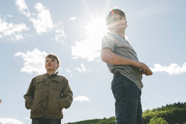 Portrait of boys standing against blue sky