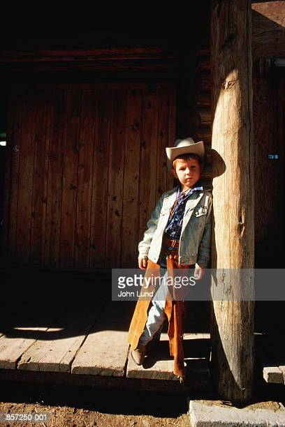 Portrait of boy(5-6)wearing cowboy costume standing outdoors