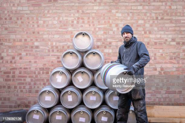 portrait of brewer by stack of barrels in small brewery - brewery stock pictures, royalty-free photos & images