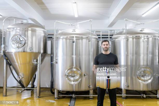 portrait of brewer with barrel in small brewery - brewery stock pictures, royalty-free photos & images