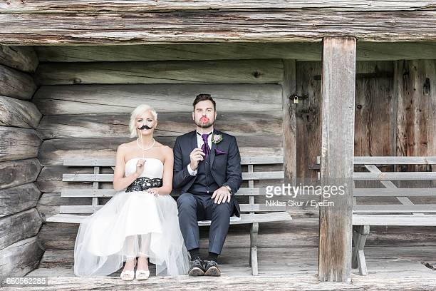 Portrait Of Bride And Groom Holding Artificial Mustache And Lips While Sitting On Bench