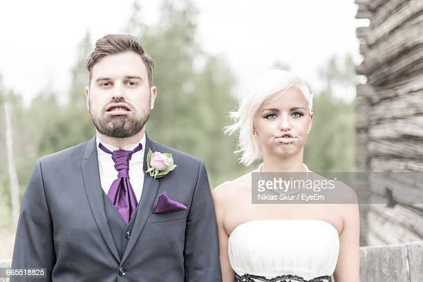 Portrait Of Bride And Groom Making Face In Yard
